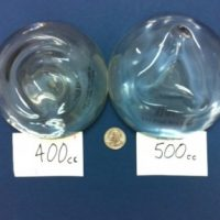 400 cc and 500 cc breast implants compared to the size of a quarter.