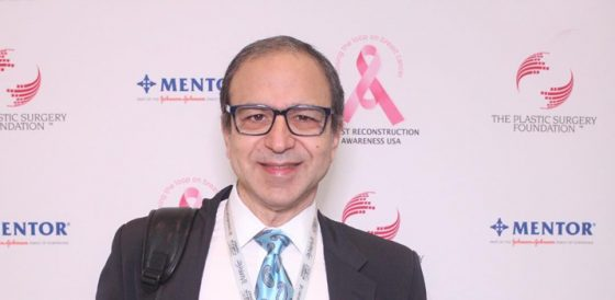 Dr. Rodriguez standing in front of a breast reconstruction awareness backdrop at a plastic surgery conference