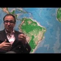 Dr. Ricardo L. Rodriguez sitting down in front of a world map.