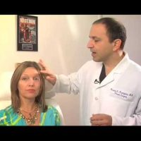 Dr. Ricardo L. Rodriguez showing the area on a patient's face that will be treated.