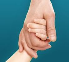 A child's hand holding an adult's hand.